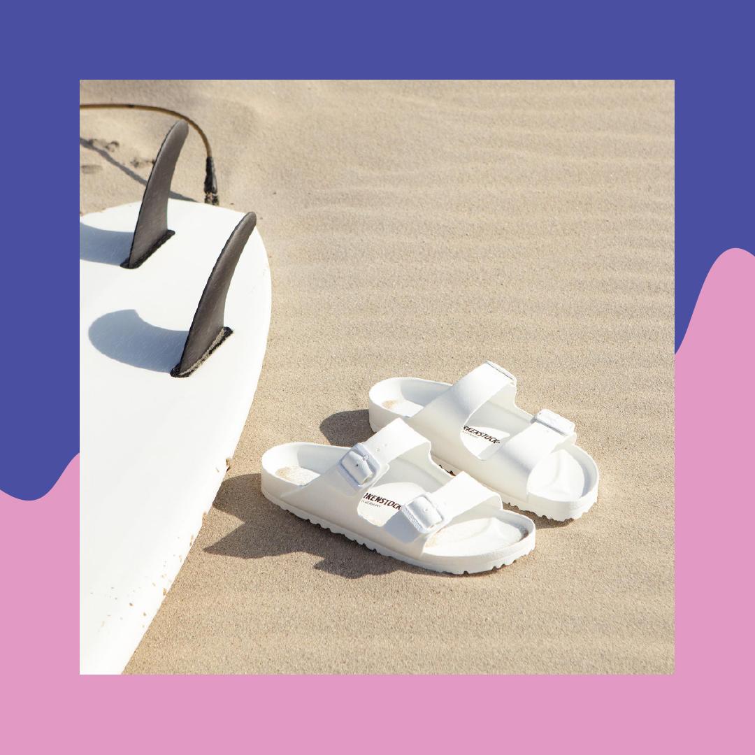 strand mit weißen arizona birkenstock und surfbrett