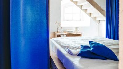 Lichtdurchflutetes Schlafzimmer mit baluen Kissen und Vorhängen